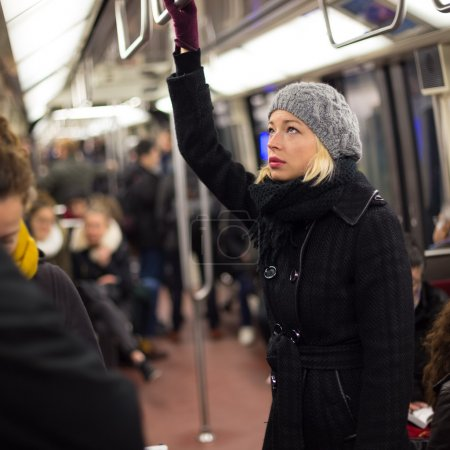 Photo pour Belle dame blonde caucasienne porte manteau hiver voyager en métro en heure de pointe. Les transports en commun. - image libre de droit