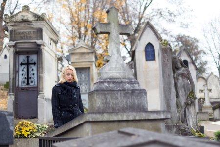 Photo pour Femme solitaire en deuil devant une pierre tombale, se souvenant de parents décédés dans le cimetière du Père Lachaise à Paris, France . - image libre de droit