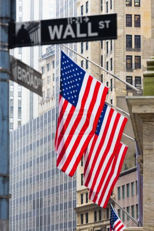 Photo for Wall street sign in New York with American flags and New York Stock Exchange background. - Royalty Free Image