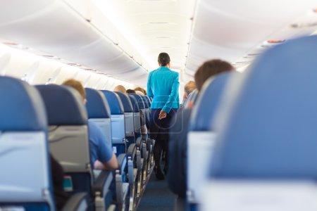 Photo pour Intérieur de l'avion avec des passagers sur les sièges et hôtesse de l'air le couloir de marche. - image libre de droit