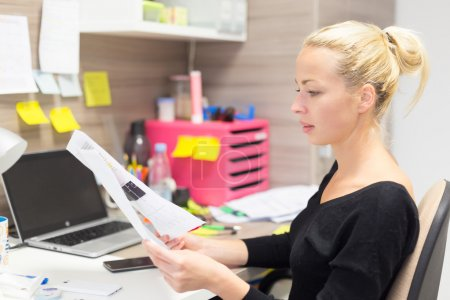 Photo for Business and entrepreneurship consept. Beautiful blonde business woman working in colorful modern creative working environment reviewing some papers. - Royalty Free Image