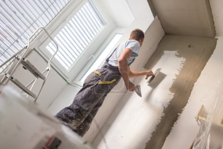 Thirty years old manual worker with wall plasterin...