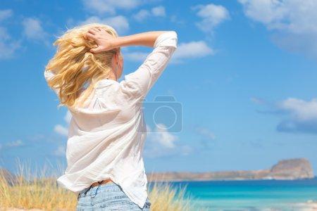 Photo pour Femme détendue jouissant de la liberté et de la vie une belle plage de sable fin. Jeune femme se sentant libre, détendu et heureux. Concept de liberté, de bonheur, de plaisir et de bien-être. Profiter du soleil en vacances . - image libre de droit