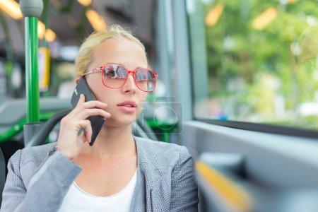 Photo pour Femme d'affaires caucasien blonde parler sur téléphone portable, voyager en bus. Transports et déplacements au travail. - image libre de droit