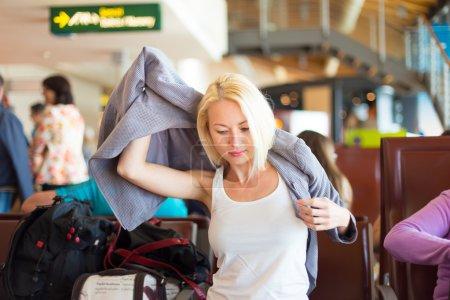Female traveler putting on her jacket.