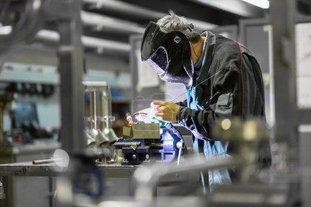 Photo pour Travailleur industriel avec masque de protection éléments inox de soudage dans les structures en acier atelier de fabrication . - image libre de droit