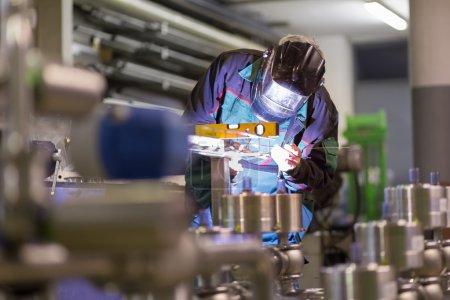 Photo pour Atelier de fabrication d'ouvrier industriel avec masque de protection soudure inox des éléments de structures en acier. - image libre de droit
