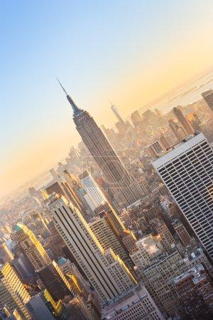 Photo pour New York City. Horizon du centre de Manhattan avec lumineux Empire State Building et de gratte-ciels au coucher du soleil vu du haut de la terrasse d'observation de Rock. Composition verticale. - image libre de droit