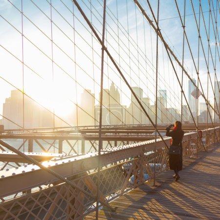Photo pour Femme de prendre une photo du pont de Brooklyn. Skyline du centre-ville de New York City Manhattan au coucher du soleil avec des gratte-ciel illuminé sur East River panorama vu du pont de Brooklyn. - image libre de droit
