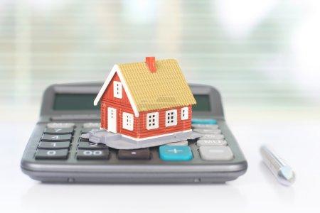 Photo pour Investissement immobilier. Maison et calculatrice sur table . - image libre de droit