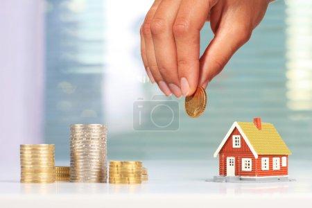 Photo pour L'investissement immobilier. Maison et pièces de monnaie sur la table. - image libre de droit