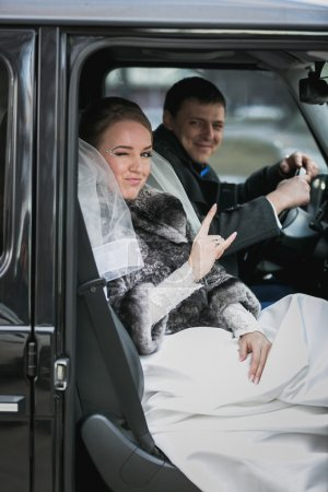 Portrait of happy bride and groom posing in car