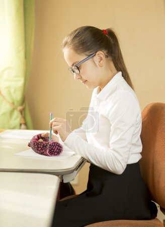 Photo for Portrait of schoolgirl sitting behind table and taking pencil out of pencil case - Royalty Free Image