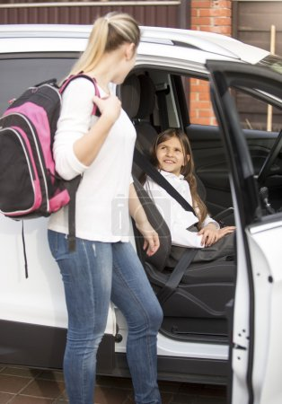 Mother looking in daughter sitting in car