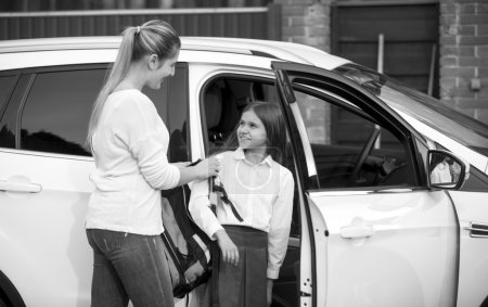 Black and white portrait of schoolgirl getting in car and giving