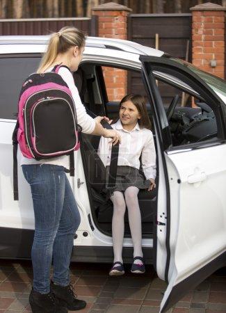 Photo pour Jeune mère aidant sa fille à monter dans la voiture après les cours - image libre de droit