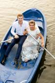 Newly married couple riding on rowing boat at evening