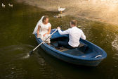 Newly married couple riding on rowing boat on lake