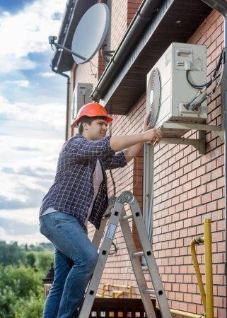 Photo pour Portrait de jeune technicien réparation en dehors de l'unité de conditionnement d'air - image libre de droit