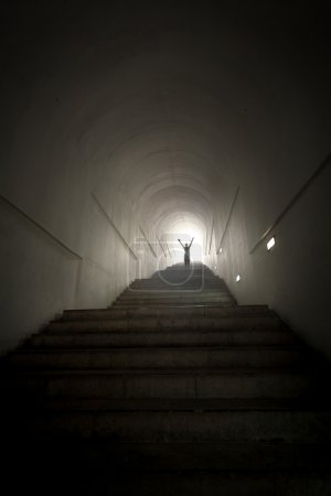 Photo for Conceptual photo of person standing in the end of tunnel at light beam with hands raised - Royalty Free Image