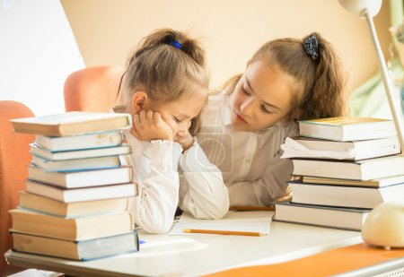 Portrait two cute girls being sad of hard homework...