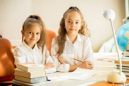 Cute girls in school uniform sitting at desk and doing homework