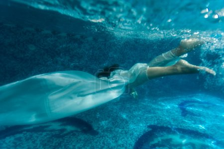 Beautiful woman wearing white fabric diving in pool