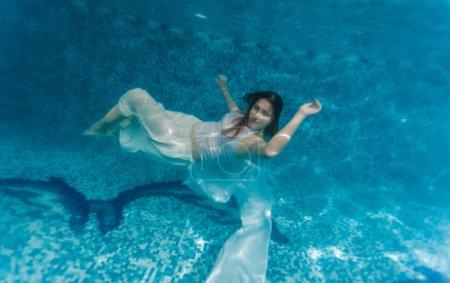 Photo pour Plan sous-marin de la femme en tissu blanc nageant sous l'eau - image libre de droit