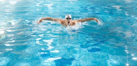 Handsome athlete swimming in poll at butterfly style