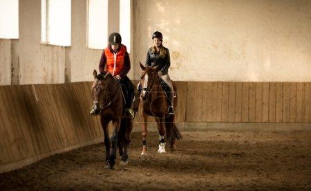 two woman jockeys doing training in riding hall