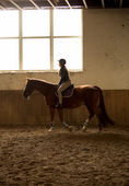 woman riding horse at indoor manege with big window