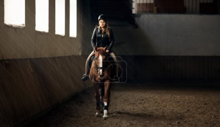 photo of woman riding horse on manege in riding hall