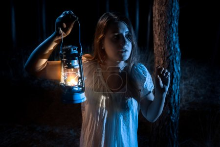 portrait of scared woman lost in forest lighting up the way with