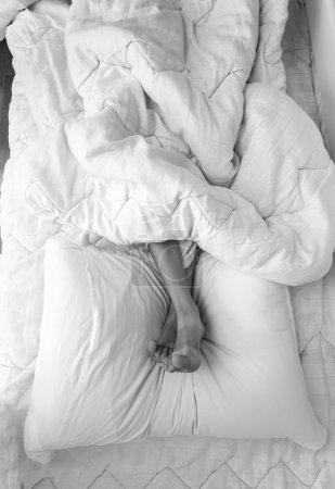 Foto de Foto blanco y negro de pies de chicas tumbado en la almohada en la cama - Imagen libre de derechos