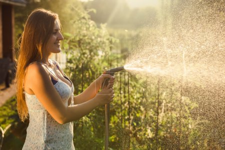 beautiful brunette woman watering garden bed with vegetables
