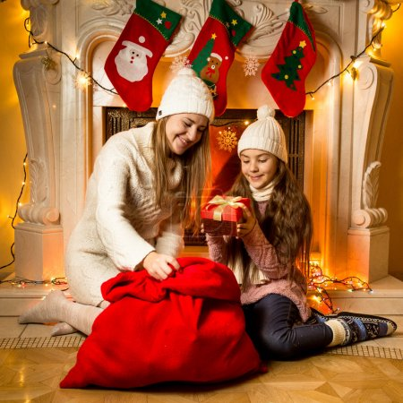 Portrait of beautiful mother and daughter looking at Christmas g