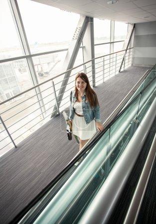 Photo pour Belle jeune femme avec sac à main marchant à l'aérogare moderne - image libre de droit