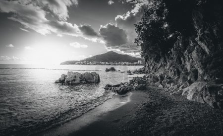 Black and white landscape of cliffs  standing at sea at sunset