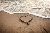 Toned photo of heart drawn on sand being washed by wave