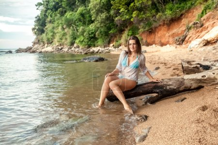 Photo for Beautiful sexy woman sitting on big branch on sea shore - Royalty Free Image