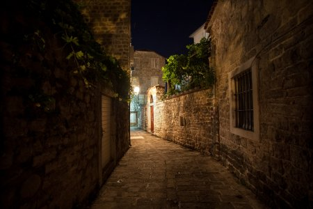 Photo for Long old narrow street lit by gas lanterns at night - Royalty Free Image