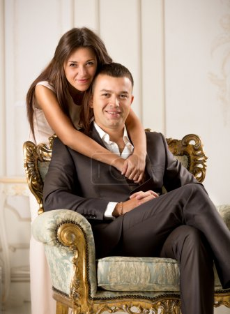 interior of happy young wife hugging husband sitting on chair