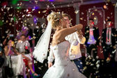 Blonde Braut tanzen im Restaurant in fliegenden Konfetti