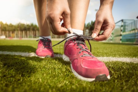 Woman tying laces on sneakers on grass field