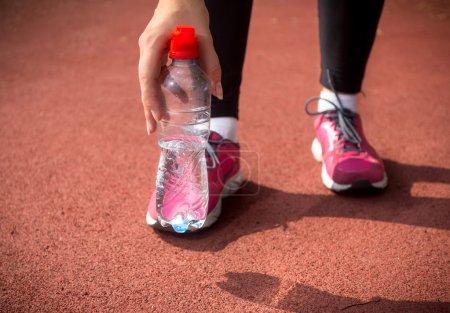 Photo pour Gros coup de coureur de femme tenant une bouteille en plastique d'eau sur la piste de course - image libre de droit