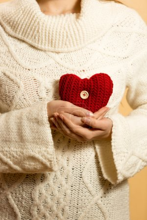 Photo for Closeup photo of woman holding red heart on chest - Royalty Free Image
