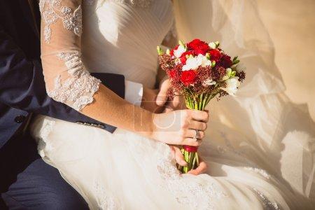groom hugging bride holding wedding bouquet