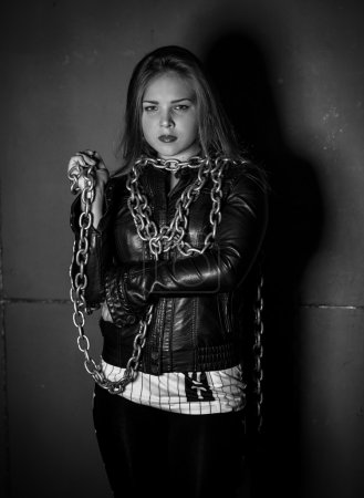 Monochorme portrait of sexy woman in leather jacket with chains