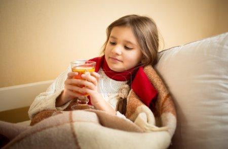 Photo pour Portrait de fille mignonne a eu la grippe et tenant une tasse de thé au lit - image libre de droit