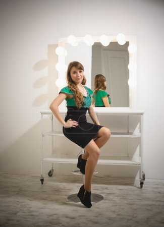 woman sitting on chair at dressing room with mirror with bulbs